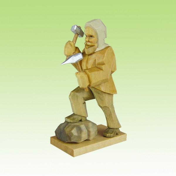 geschnitzter Bergmann, hackend, Fuß auf Stein